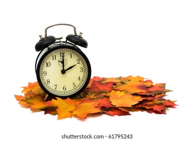 Retro black alarm clock on fall leaves, Fall Time change