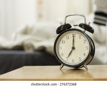 Retro black alarm clock show 7 o'clock in the morning for wake up.Background is a bedroom.