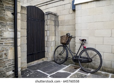 Retro black bycicle parked near wall in small British village