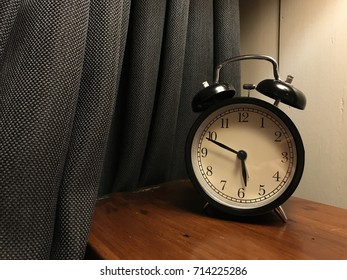The retro black circle alarm clock put on the wooden table beside with grey curtain on ten past six