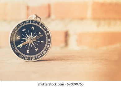 The retro black and silver compass on the wood ground against classic rock wall  blurred background with sunlight. Vintage style and filtered process. Selective focus.