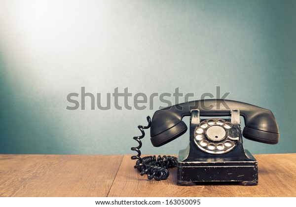 Retro black telephone on wooden table in front gradient background