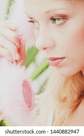 Retro blond woman holding old fashion pink phone with feathers.