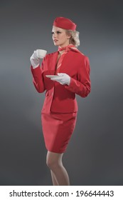 Retro blonde stewardess wearing red suit with cap. Holding cup of coffee. Studio shot against grey.