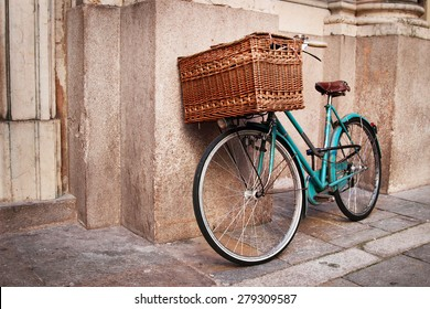 Retro blue bike with big basket on the street of the old town, Italy.