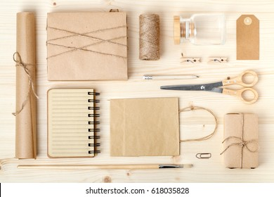 retro branding for mock up template design. vintage wrapped gift boxes, paper bag, notebook and wrapping tools on wooden background. mail and handicraft concept. above view. flat lay