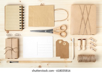 retro branding for mock up template design.vintage wrapped gift boxes, paper bag, postcard, notebook and wrapping tools on wooden background. mail and handicraft concept. above view. flat lay