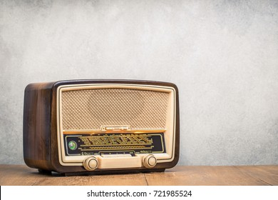 Retro broadcast radio receiver with green eye light on wooden table circa 1950 front concrete wall background. Listen music concept. Vintage instagram old style filtered photo