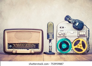 Retro broadcast radio receiver, reel to reel tape recorder circa 60s, microphone and headphones on wooden table front concrete wall background. Vintage style filtered photo