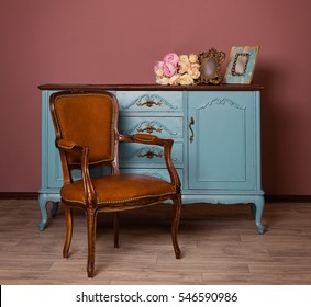 Retro brown leather armchair near blue dresser, tender bouquet and two frames. Blue and brown vintage interior. Brown room with ethnic dresser and chair. Antique cupboard. Clothes closet. Vanity Table