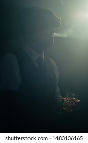 Retro businessman with cap smokes cigarette in smoky room.