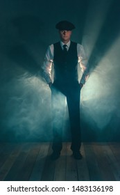 Retro businessman with cap standing in smoky room.