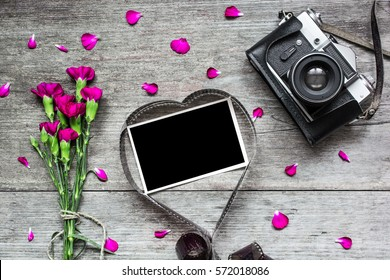retro camera and blank photo frame in heart shaped film with purple carnation flowers, petals and gift box on rustic wooden background. valentines day background. top view