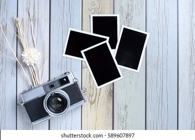 Retro camera and empty old instant paper photo album on wood background, top view (vintage style)