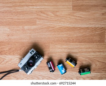 Retro camera and film cartridges laying on the bottom part in wooden background for montage product display on top view