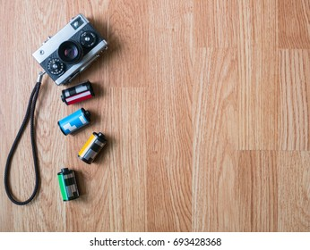 Retro camera and film cartridges laying vertically in wooden background for montage product display on top view or poster advertorial