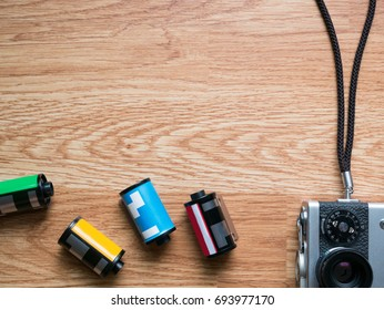 Retro camera and film cartridges laying horizontally in wooden background for montage product display on top view