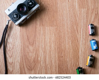 Retro camera and film cartridges in wooden background for montage product display on top view