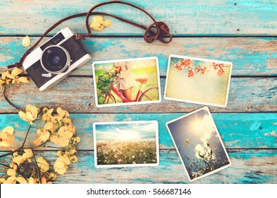 Retro camera and instant paper photo album on wood table with flowers border design - photo of remembrance and nostalgia in spring. vintage style