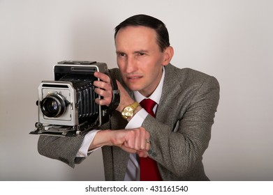 Retro camera man in grey jacket and red tie sitting against white background.