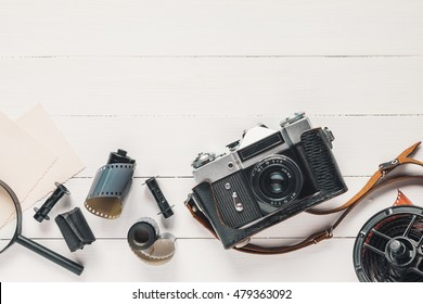 Retro camera, old photo film rolls, empty photos and magnifier on wooden background. Flat lay, top view.