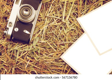 Retro camera on hay rural background with two blank photos isolated with clipping paths
