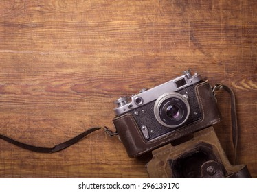 Retro camera on wood table background, vintage color tone