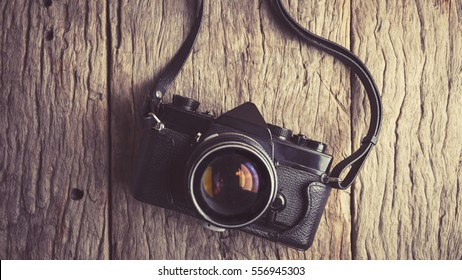 Retro camera on wood table background, vintage color tone.