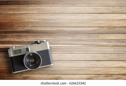 Retro camera on wood table background, vintage color tone. top view with copy space for use