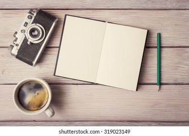 Retro camera, open memo book and cup of coffee on rustic wooden desk