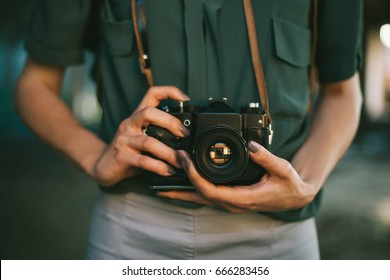 Retro camera photographer close up. Midsection of female photographer