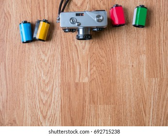 Retro camera pointing at the center of the image and film cartridges in wooden background for montage product display on top view