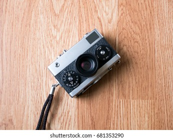 Retro camera in wooden background on top view