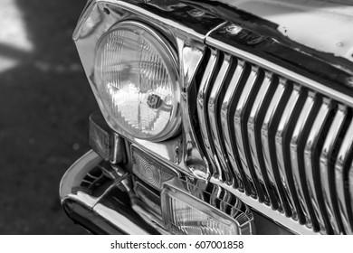 Retro car fronl light. Old monochrome style photo.