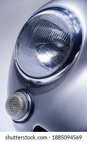 Retro car headlight with chrome parts on hood, vintage vehicle with silver bodywork, classic sedan, automobile industry