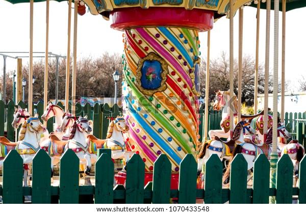 Retro carousel in empty closed fairground. Close up crop