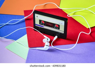 Retro cassette tape rubber with earphones on a colored background