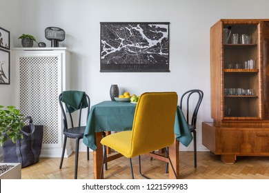 Retro china cabinet in eclectic living room interior with yellow chair and map on the wall, real photo