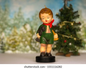A retro Christmas diorama of a vintage little boy figurine candle with a miniature Christmas tree and snowy winter forest scene in the background