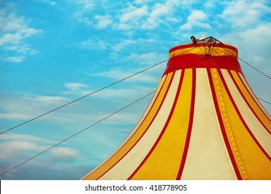 Retro circus concept. Old vaudeville circus tent top. Red, white and yellow stripes with blue sky and white clouds above. Copy-space. Postcard style. Outdoor shot