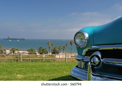 A retro classic car with the USS Ronald Reagan in the background in Santa Barbara, California.