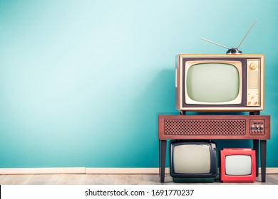 Retro classic old analog TV receivers set and aged wooden television stand with outdated amplifier front gradient mint blue wall background. Broadcasting, news concept. Vintage style filtered photo