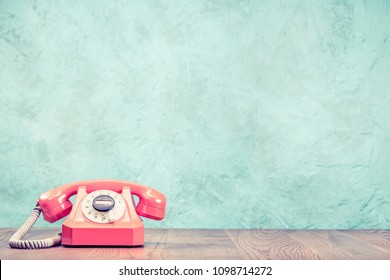 Retro classic outdated pink rotary telephone on wooden desk front textured aquamarine concrete wall background. Vintage instagram old style filtered photo