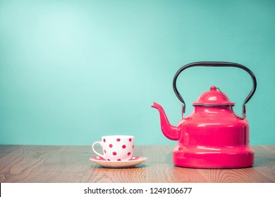 Retro classic red kettle and cup of tea with polka dots on oak wooden table in front aquamarine wall background. Vintage old style filtered photo