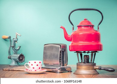 Retro classic red kettle on gas stove, a cup of tea, outdated bread toaster, kitchen board and vintage manual meat chopper on oak wooden table in front mint green background. Old style filtered photo