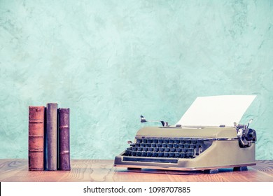 Retro classic typewriter with sheet of paper and old books on wooden table front aquamarine concrete wall background. Vintage style filtered photo