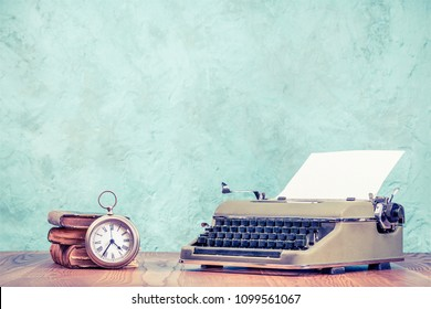 Retro classic typewriter with sheet of paper, old books and big silver pocket watches design clock on wooden table front aquamarine concrete wall background. Vintage style filtered photo