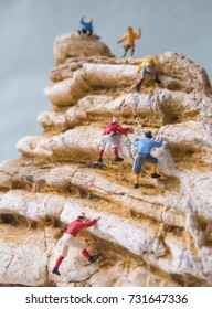 Retro climbers climbing a peak - miniature toy figures.(focused on the middle climber)