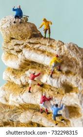 Retro climbers climbing a peak - miniature toy figures. (selective focus at the top blue jacket climber)
