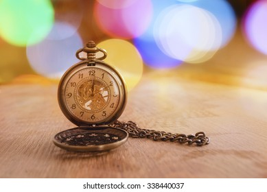 Retro clock with bokeh on wooden background